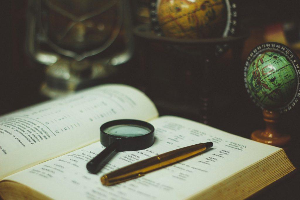 Libro, lupa y estilográfica.